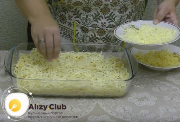 Выкладываем спагетти в смазанную маслом форму и посыпаем половиной сыра.