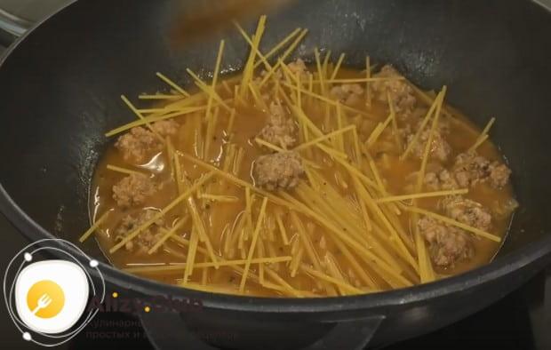 Ломаем спагетти пополам и кладем в сковороду.