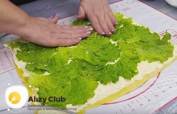 По всей поверхности заготовки раскладываем листья салата.