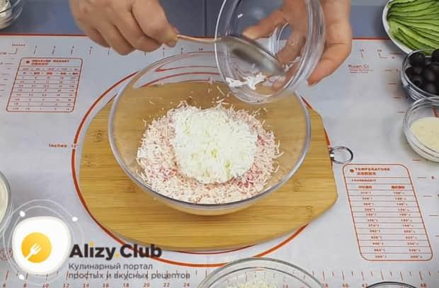 К крабовым палочкам добавляем натертые на мелкой терке яичные белки.