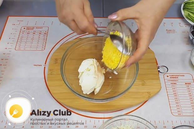 Отдельно перемешиваем сливочный сыр с натертыми на мелкой терке желтками.