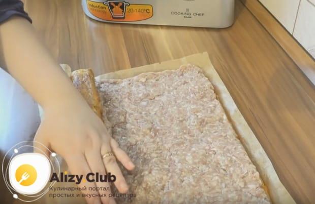 Ровным слоем выкладываем на пласт сыра фарш и скручиваем рулет.
