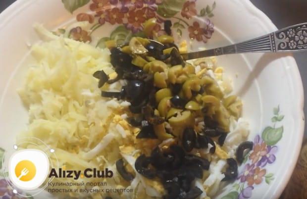 Добавляем оливки к натертым на крупной терке картофелю и яйцам.
