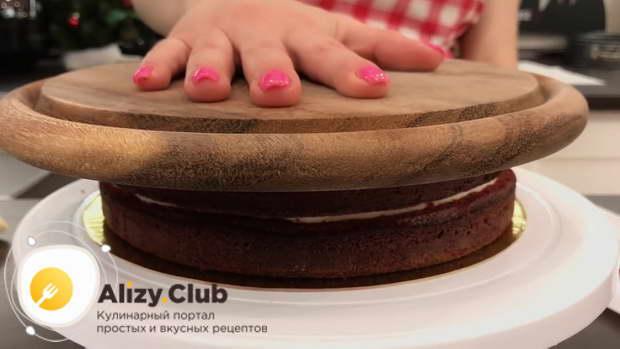 Кладем сверху на торт кухонную доску и легонько прижимаем рукой