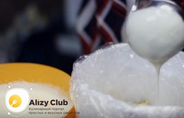 Складывая кусочки рулета в застеленную пищевой пленкой форму, заливаем их кремом.