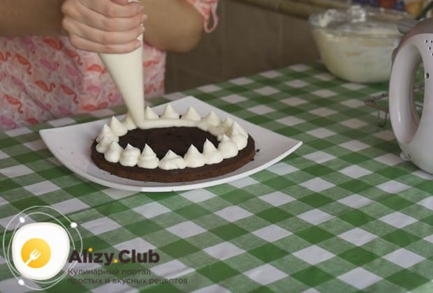 При помощи кондитерского мешка отсаживаем на край торта кремовые капельки, а середину коржей просто заполняем кремом.