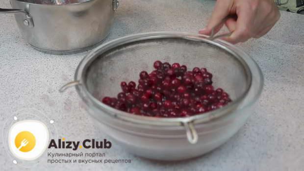 Спустя время, ягоды клюквы перекладываем в сито, чтобы стекла лишняя жидкость