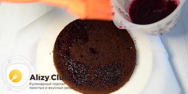 Кладём первый бисквит и смазываем его поверхность вишнёвым сиропом