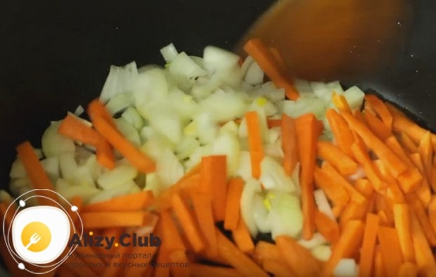 Выкладываем в казан лук и морковку.