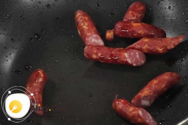 Для приготовления тушеной капусты с мясом обжарьте колбаску