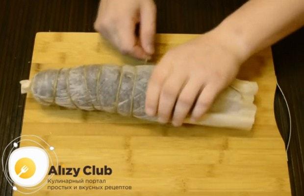 Обвязываем мясо в пергаменте бечевкой.