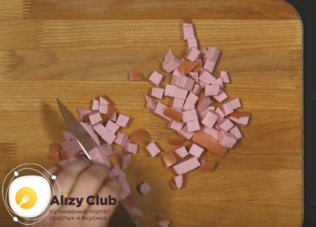 Мелким кубиком нарезаем колбасу.