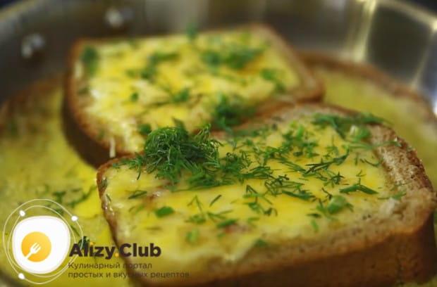 Яичница в хлебе с колбасой и сыром будет еще красивее, если посыпать ее свежей зеленью.