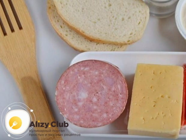 Колбасу, сыр и хлеб режем тонкими ломтиками.