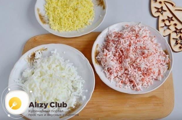 Отдельно на мелкой терке натираем белки и желтки отваренных вкрутую яиц, а также крабовые палочки.