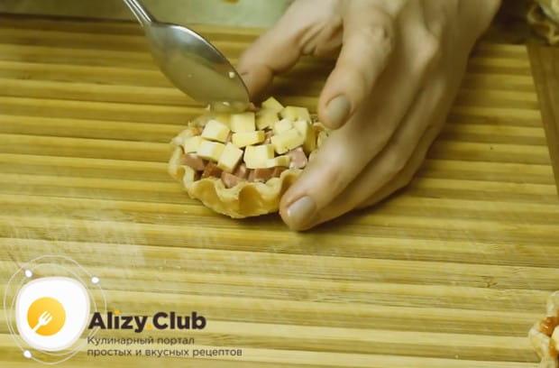 Выкладываем колбасу, а сверху размещаем кубики твердого сыра.
