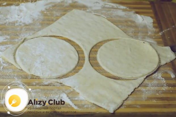 Немного раскатываем тесто и чашкой или стаканом вырезаем из него кружочки.
