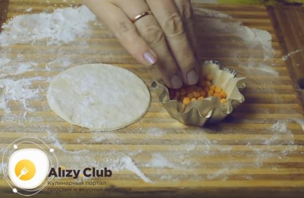 В каждую формочку кладем листик пергамента и насыпаем на него горох или фасоль.
