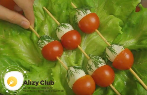 Выкладываем закуски на блюдо, застеленное листьями салата.