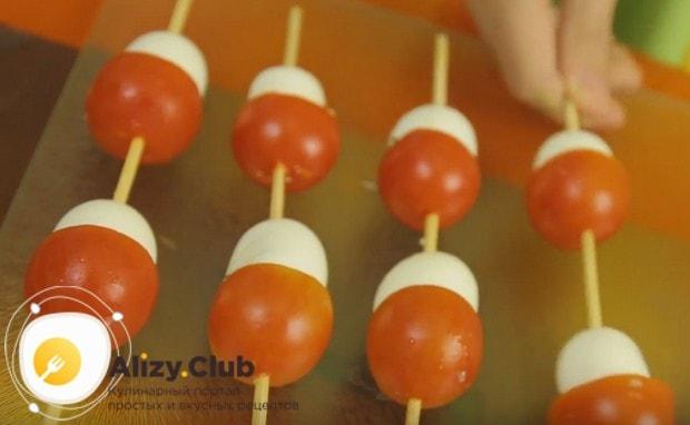 Аккуратно нанизываем нафаршированные яйца на шпажки, а поверх них нанизываем помидорки, формируя грибочки.