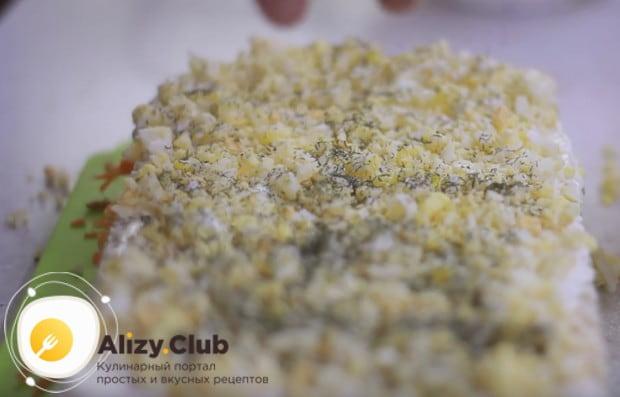 Выкладываем слой измельченных яиц, перемешанных с сушеным укропом.