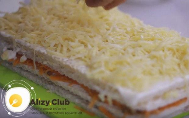 Сверху посыпает торт тертым сыром.