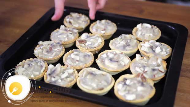 Выложите приготовленный жульен в 12 готовых тарталеток и в 6 приготовленных вами