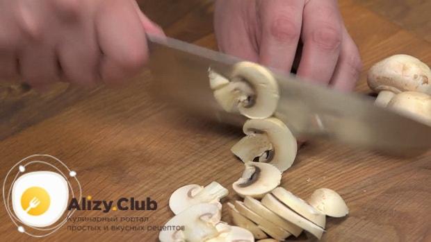 Для приготовления яичницы с беконом нарежьте грибы.