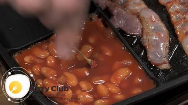Для приготовления яичницы с беконом обжарьте фасоль.