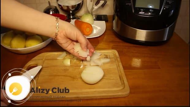 Нарежьте лук для приготовления свиных ребрышек с картошкой в мультиварке