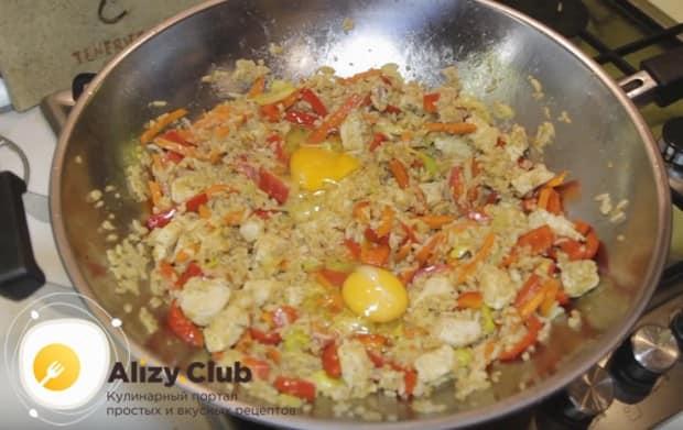 Через несколько минут возвращаем на сковороду курицу и выбиваем туда же два яйца.