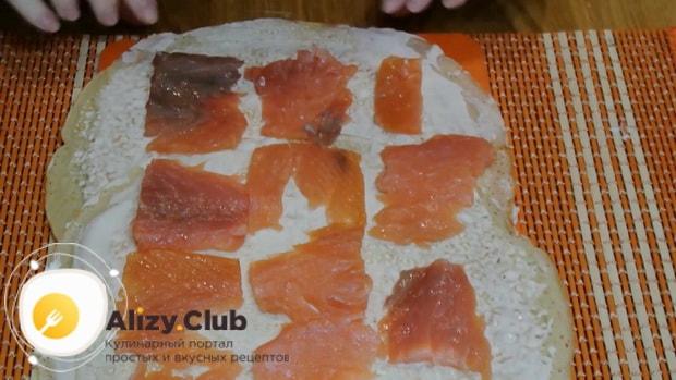 Для приготовления блинов с красной рыбой и сливочным сыром, выложите ингредиенты на блины