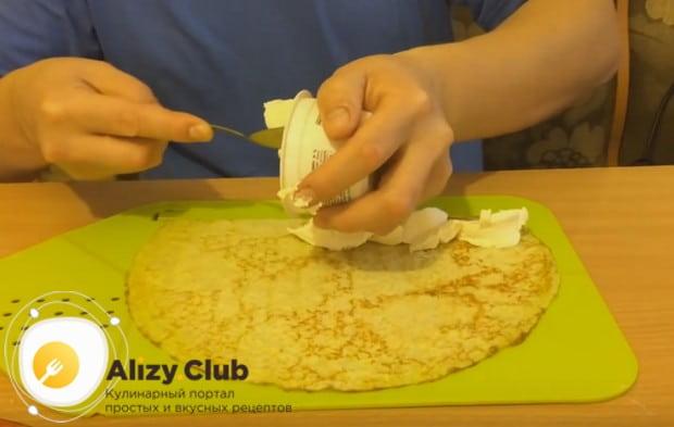 На один конец блина колбаской выкладываем сливочный сыр.