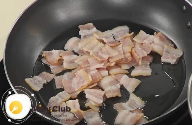 Затем сливаем с бекона воду и обжариваем его на сковороде, чтобы получить шкварки.
