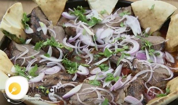 Посыпаем блюдо полукольцами красного лука, зеленью, а по краю сковороды раскладываем треугольнички лепешек.
