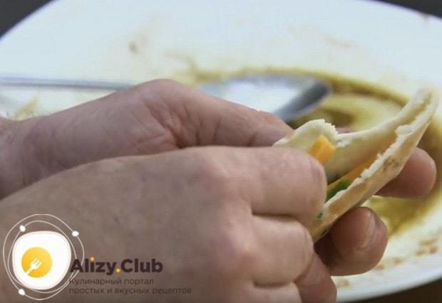 Теплые лепешки разрезаем пополам и внутрь закладываем кинзу и кусочек сыра.