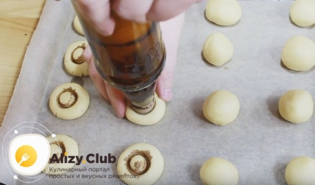 Горлышком бутылки придавливаем шарики теста на противне, формируя из них таким образом грибочки.
