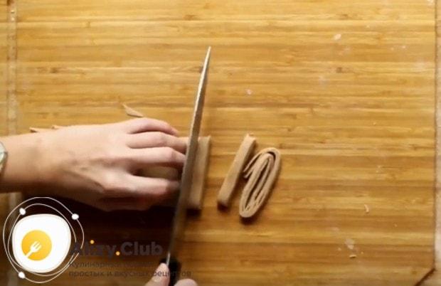 Тесто тонко раскатываем, затем складываем внахлест и нарезаем лапшу.