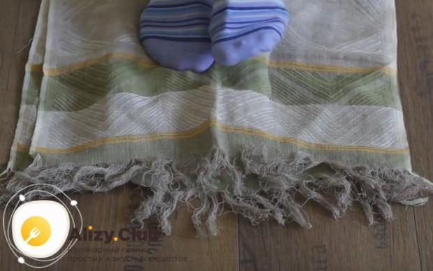 Накрываем тесто второй половиной полотенца и месим ногами.