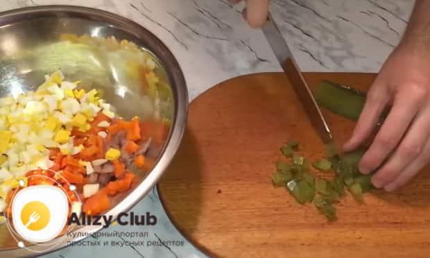 Для приготовления закуски из рубленой селедки нарежьте огурцы