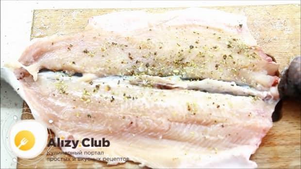 Перед тем как запечь форель в духовке целиком, добавьте к рыбе специи