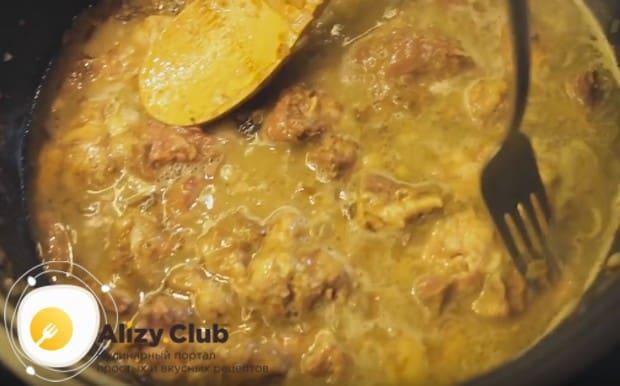 В сковороду выкладываем тушенку, разбиваем кусочки мяса.