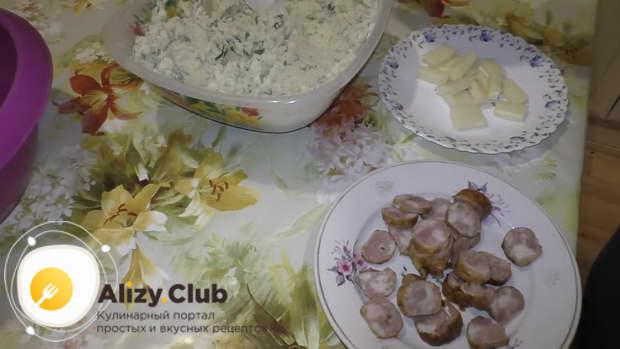 Нарезать тонкими ломтиками 200 г колбасы для начинки
