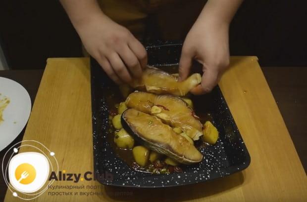 Теперь выкладываем картошку на противень, а на не раскладываем стейки.