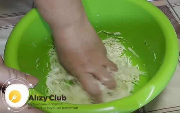 Хорошенько разминаем капусту с солью.