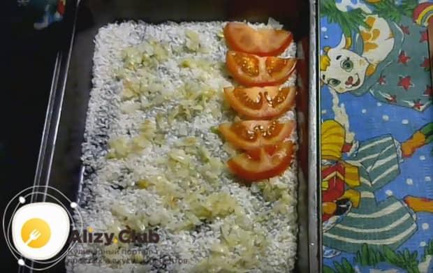 Поверх риса выкладываем слой лука, а на него слой помидоров.