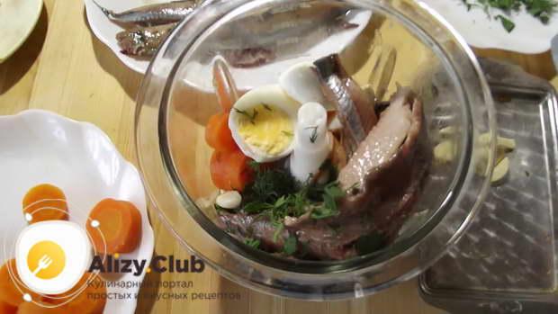 Складываем ингредиенты в чашу блендера в таком порядке: морковь, яйца, зелень, селедка, чеснок