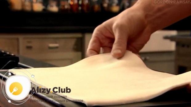 Лист слоеного теста раскатываем на листе пергаментной бумаги