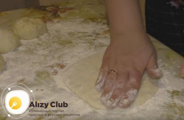 Разминаем тесто руками в лепешку.