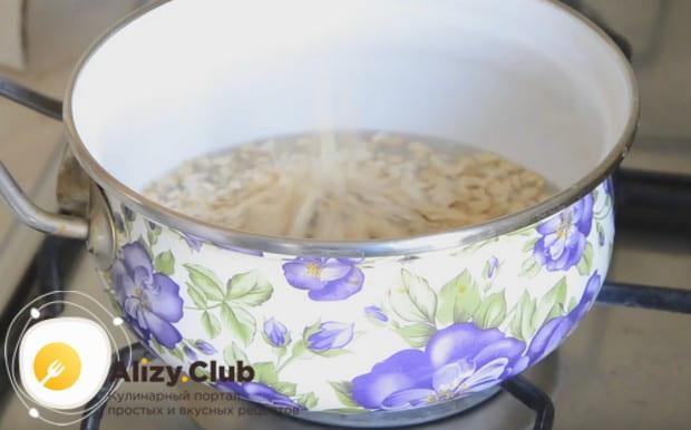 Оладьи будем готовить из овсяной каши, поэтому наливаем в сотейник воду и насыпаем хлопья.